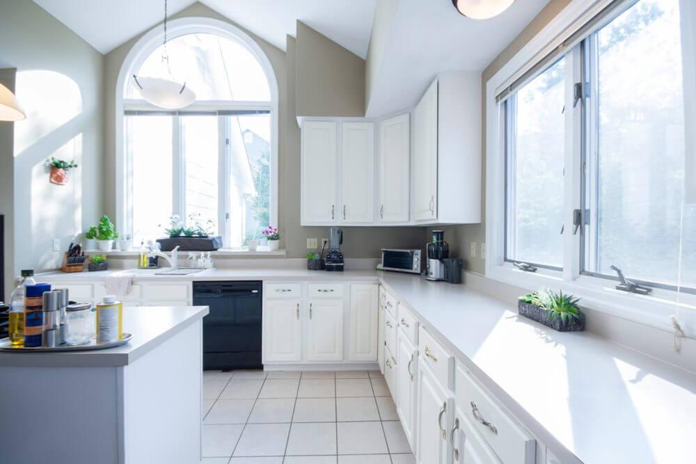 Белая кухня с деревянной столешницей и бежевыми стенами