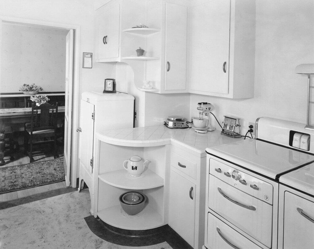 Кухня с белым глянцем на столешнице с входом в столовую