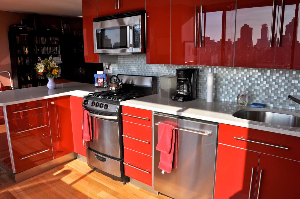 Красно-белая кухня в сочетании с мозаичным фартуком и хромированной отделкой