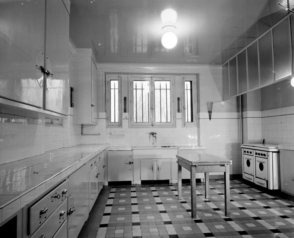 Белая глянцевая кухня с интересным черно-белым полом из плитки